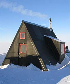 REDUCED TO ASHES: The timber and bitumen hut was a favourite haunt of Sir Ed, shown outside it during his 2007 visit to Antarctica. Image www.stuff.co.nz