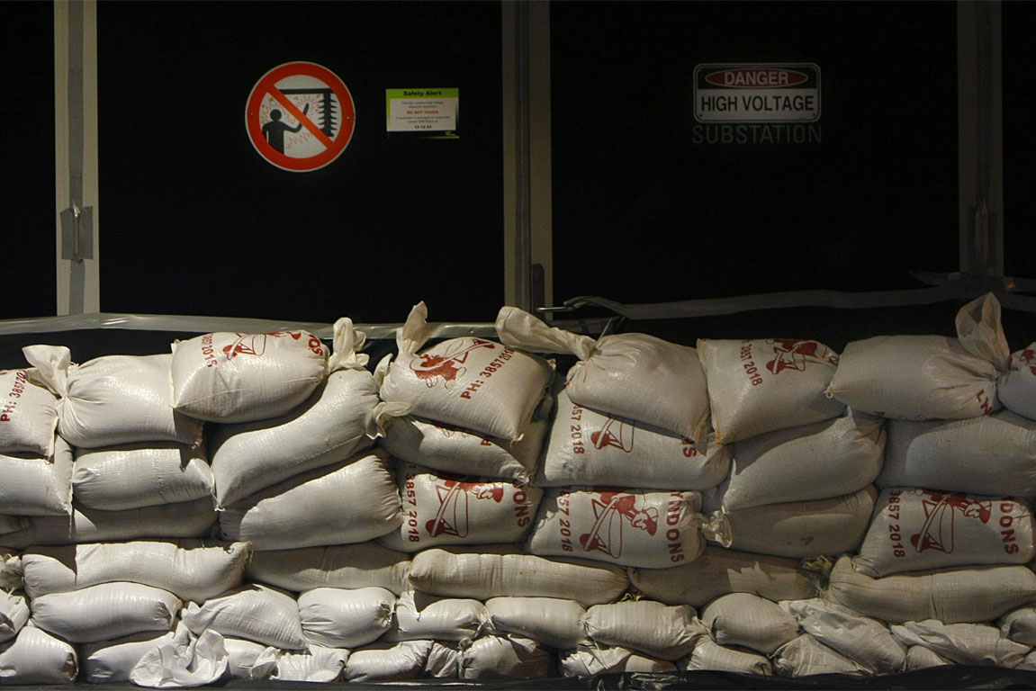 Sandbags are seen stacked in front of an electrical substation in Brisbane