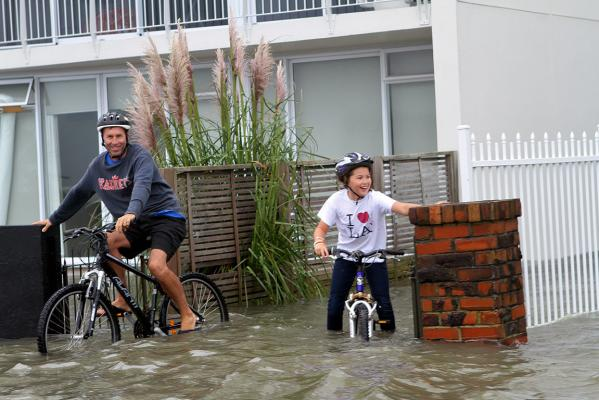 Cyclists struggle through floodwaters in Auckland.
