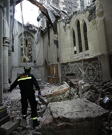 IN RUINS: A member of a New Zealand Urban Search and Rescue team examines an area of the inside of Christ Church Cathedral.