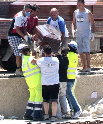 Rescuers put a coffin on a truck at the dock in Lampedusa, Italy, following the death of 25 African migrants who tried to reach Italy from Libya.