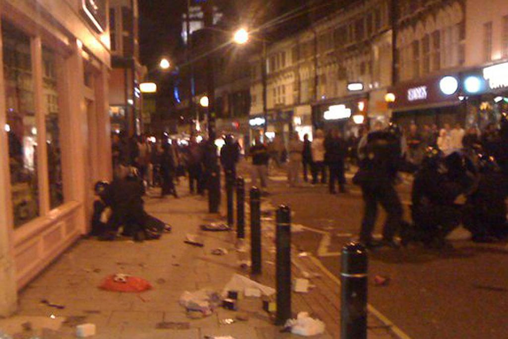 Police tackle rioters outside Alex Spence's London home.