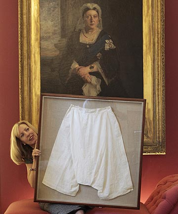Kate Bain from Lyon and Turnbull auctioneers poses with a framed pair of silk bloomers that once belonged to Queen Victoria that have been sold at auction for over $18,000.