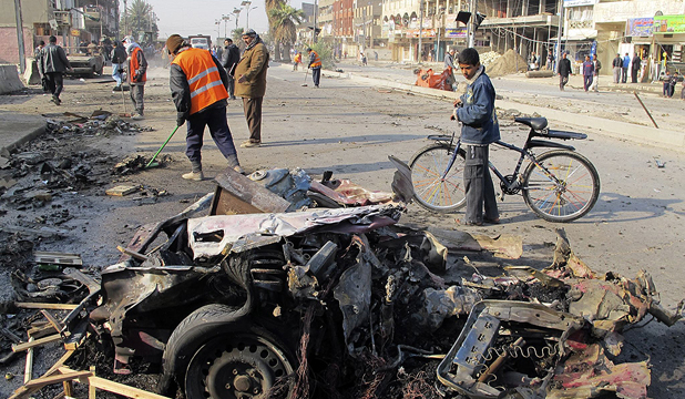 VIOLENCE FLARES: A boy stands near the site of a car bomb attack in Baghdad's Shaab District on Thursday.