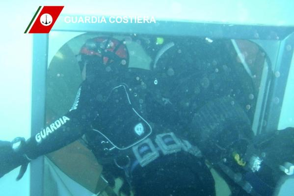 An Italian Coast guard diver inspects the Costa Concordia cruise ship that ran aground off the west coast of Italy, at Giglio island.