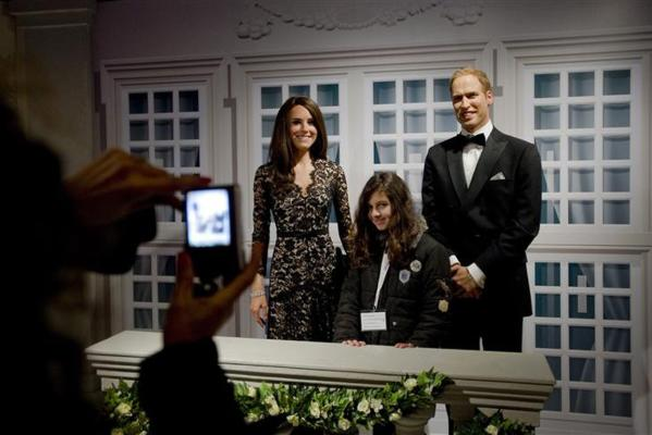 Visitors pose with waxwork models of Britain's Royal couple William and Catherine, the Duke and Duchess of Cambridge, at Madame Tussauds in Amsterdam.