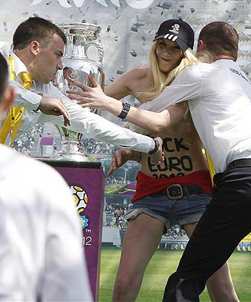Security guards detain a demonstrating activist from women's rights organisation Femen near the Euro 2012 trophy during its unveiling to the public in central Kiev.