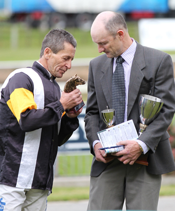 Jockey Noel Harris and trainer Alexander Fieldes inspect a trophy awarded after Marea Alta's Kiwifruit Cup win at Tauranga on Saturday.