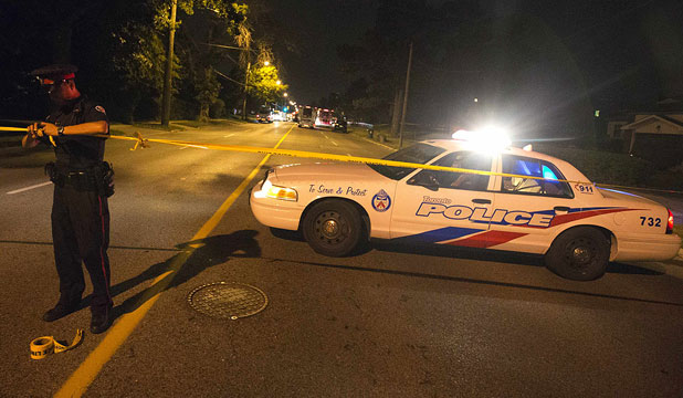 GUN VIOLENCE: A police officer tapes up a crime scene following a shooting in Scarborough, a suburb in east Toronto.