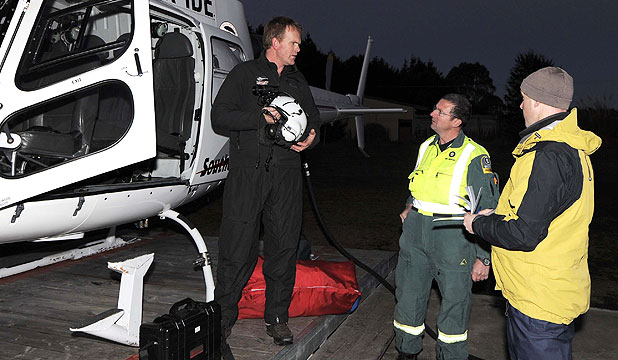 RESCUE MISSION: Southern Lakes Helicopter pilot Chris Green prepares to leave to pick up two fishermen whose boat is believed to have overturned near Chalky Inlet. St Johns medic John Lambeth and constable Glenn Matheson prepare as well.