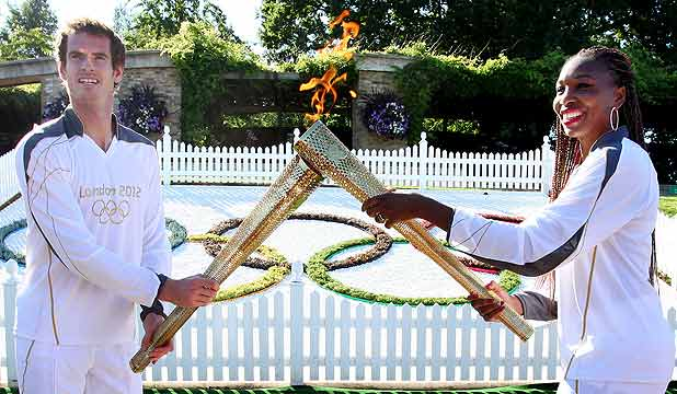 Andy Murray passes the Olympic Flame to Venus Williams at Wimbledon during day 66 of the London 2012 Olympic Torch Relay.