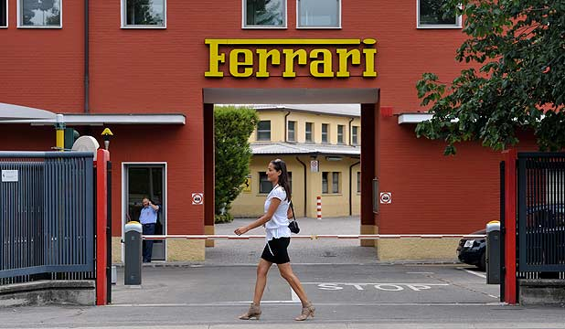 A pedestrian passes the main entrance to the Ferrari SpA headquarters and automobile plant in Maranello, Italy.