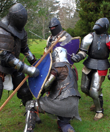 BASH, CRASH:  Medieval armoured fighters battle each other with swords and axes. Charlie Tapsell on left, Justin Stockbridge kneeling, Justin Harris on right, and Matthew Derdrachen in background.