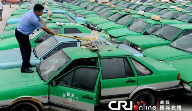 A Chinese worker begins demolition of one of 156 illegal taxis seized in the city of Hefei.