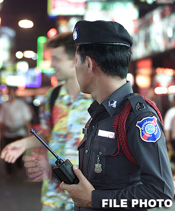 DARK SIDE: A Thai tourist police officer watches late night revellers in Pattaya. New Zealander Robert Hollick was stabbed to death in the resort town, according to a local media report.