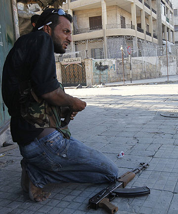 STREET FIGHTING: A member of the Free Syrian Army reloads a weapon during clashes with Syrian Army soldiers in Aleppo.