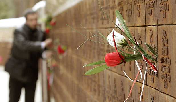TRUTH REVEALED: A man puts flowers into a wall with names of killed Polish officers during a commemoration ceremony at a memorial complex in Katyn.