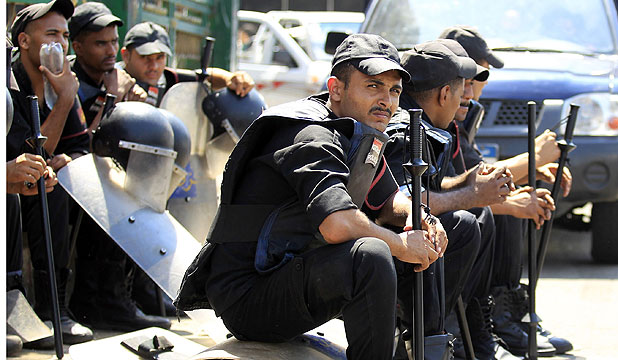 AFTER THE RIOT: Policemen rest after protesters clashed with security forces in Tahrir Square and the area around the US embassy.