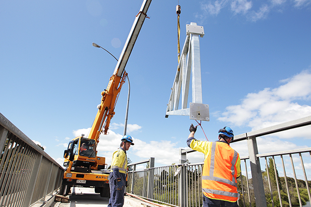 DELICATE WORK:  A crane lowers a clip-on frame off Hamiltons Pukete Bridge. Framing pairs are being attached to the southern side of the bridge to support a new clip-on pedestrian and cycle lane.