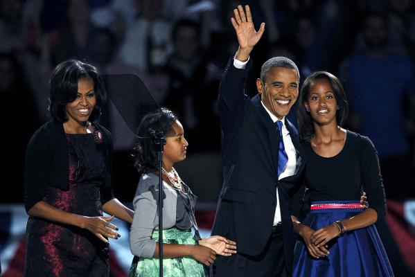 US President Barack Obama waves with his daughters Malia and Sasha, and wife Michelle, before addressing supporters
