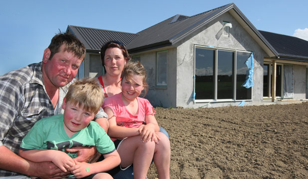 Willy and Amanda Buchanan with Michael, 5, and Sophie, 7, in front of their unfinished house at Wreys Bush.