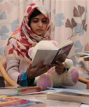 Pakistani schoolgirl Malala Yousufzai reads a book as she recuperates at the The Queen Elizabeth Hospital in Birmingham.