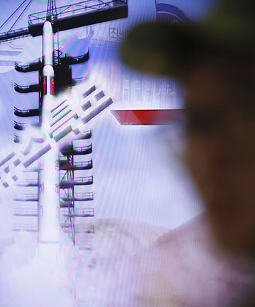 BLAST OFF: A South Korean soldier watches a television report on North Korea's rocket launch at a railway station in Seoul.