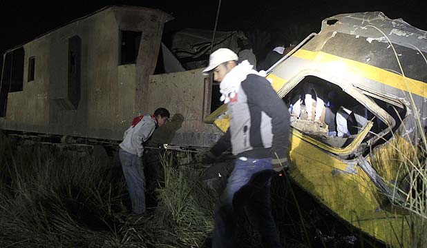 CARRYING CONSCRIPTS: People walk around the wreckage of a military train crash in the Giza neighbourhood of Badrashin.