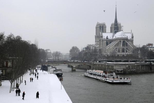 A tourist boat travels along the River Seine near the snow-covered Notre Dame Cathedral in Paris.