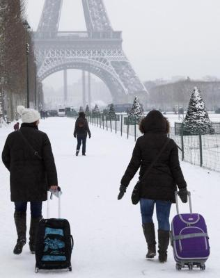 Tourists pull their luggage on a snow-covered path as they walk towards the Eiffel Tower in Paris.