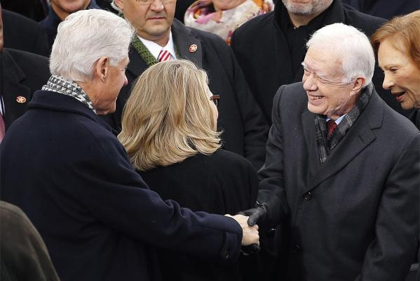 Former president Bill Clinton (L) shakes hands with former president Jimmy Carter (R) ahead of the ceremonial swearing-in ceremonies for US President Barack Obama.