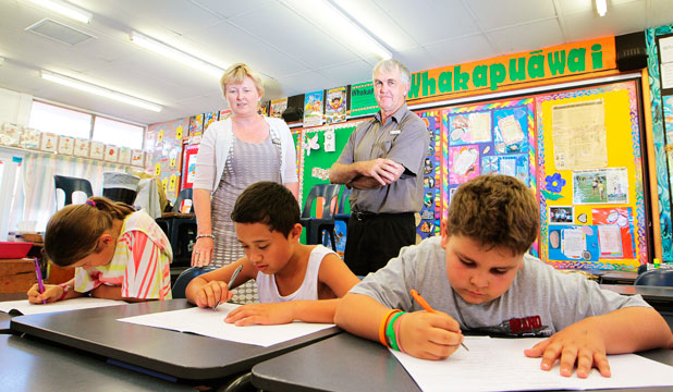 Teacher Heather Russell and principal Mr Poland stand behind pupils Georgia Mecchia, 9, Harlem Timoko-Tangaroa, 10, and Brodi Werder-Payne, 9.