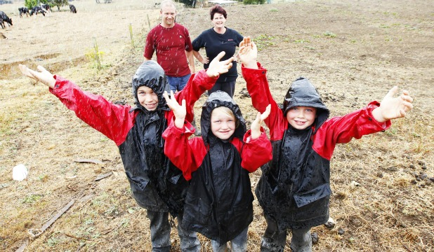 Alex, Kate and Boyd FitzGerald celebrate yesterday's downpour as parents Rob and Jacqui