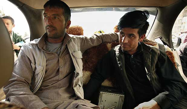 Khalid (left) and Barhanuddin regularly buy and sell used cars for their logistics company in Kabul, Afghanistan.