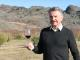Sam Neill in his Central Otago vineyard with a glass of his Two Paddocks wine.