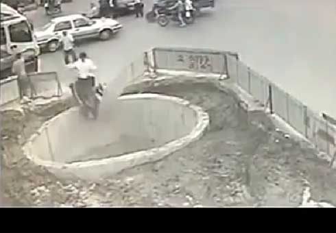 Scooter rider plunges into hole.
